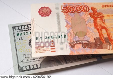The Russian Banknote Of Five Thousand Rubles Hangs Over The American Banknote Of One Hundred Dollars