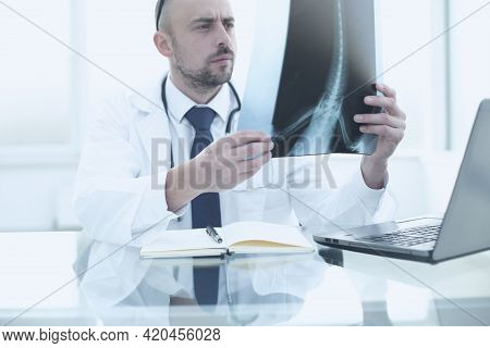 The Doctor Examines A Snapshot Of The Patients Spine In Clinic. The Concept Of High Quality Medical