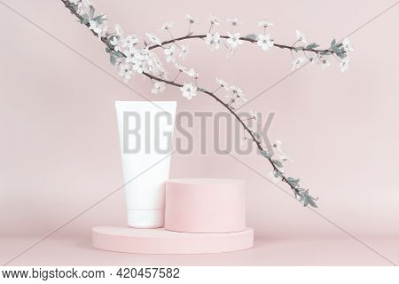 Blank White Cosmetics Tube On Round Platform Podium Stand And Spring Flowering Tree Branch With Whit