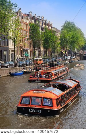 Amsterdam, Netherlands - July 7, 2017: People Ride Tour Boats At Prinsengracht Canal In Amsterdam, N
