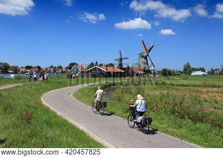 Zaanse Schans, Netherlands - July 9, 2017: Cyclists Visit Windmills Of Zaanse Schans. Netherlands Ha