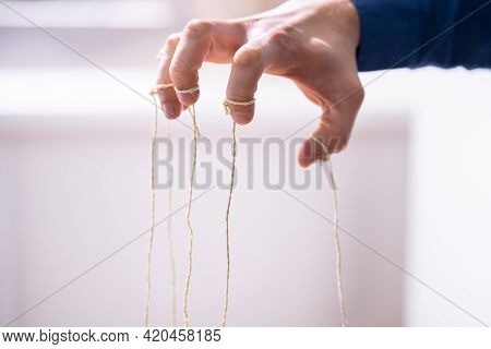 Manipulating Marionette Puppet Strings By Hand. Business Power