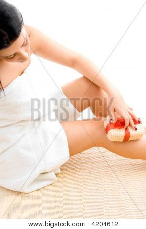 High Angle View Of Woman Scrubbing Her Legs On White Background