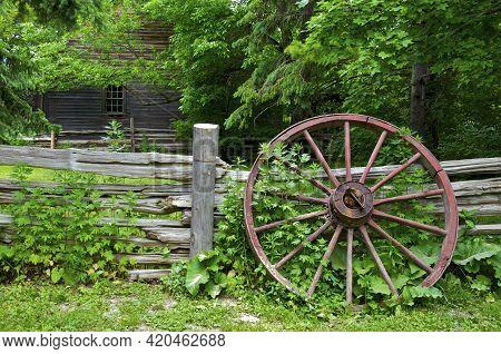 Wood Spoke Wagon Wheel Left On The Wooden Fence On A Farmhouse