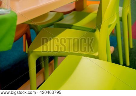 Light Green Plastic Chairs Stands Close To Each Other's Near Yellow Plastic Table. No People. Seats