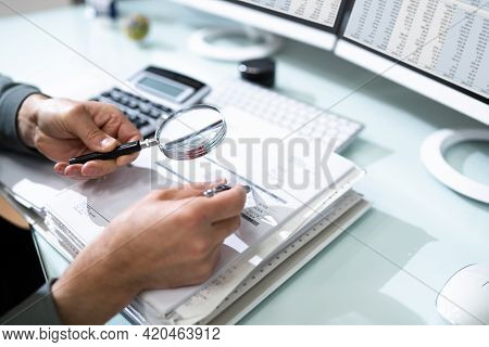Audit And Fraud Investigation. Auditor Using Magnifying Glass On Document