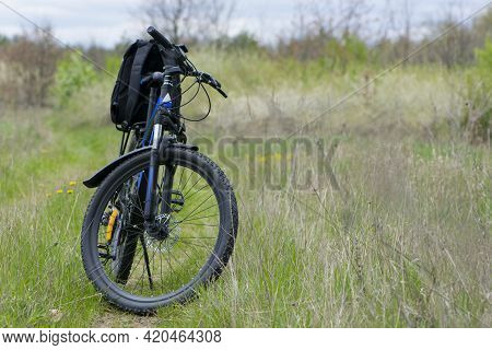 Bike Stands On In The Field. A Mountain Bike Stands On A Field Path With Green Grass. Outdoor Cyclin