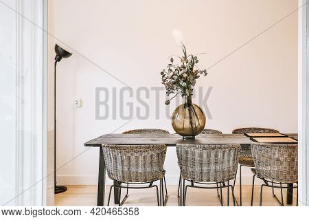 Glass Vase With Bunch Of Fresh Flowers Placed On Table With Chairs In Stylish Dining Room At Home