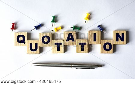 Quotation - Word On Wooden Cubes With Stationery Buttons, Pen On White Background. Business Concept