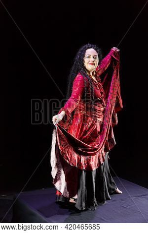 Gypsy Woman Barefoot With Long Black Hair Dances In A Red Dress On A Black Background. Vertical Phot