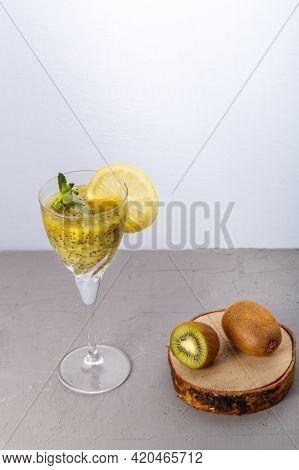 Kiwi Smoothie Garnished With Mint And Lemon In A Glass On A Gray Background Near Kiwi. Vertical Phot