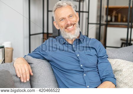 Charismatic Grey Haired Man In Smart Casual Wear Sits On The Couch And Looks At The Camera. Portrait