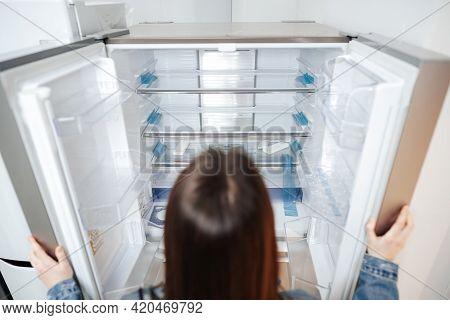 Young Attractive Woman Choosing Refrigerator In Hypermarket