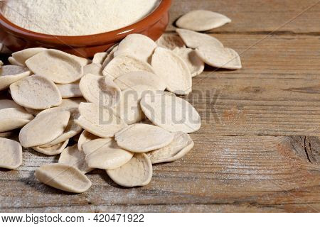 Fresh Dry Homemade Italian Pasta Strascinati With Durum Wheat Flour In A Clay Bowl On A Natural Wood