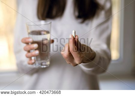 A Depressed Woman Drinks Antidepressants. A Young Woman Holds A Pill And A Glass Of Water In Her Han