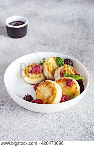 Fresh Cottage Cheese Or Ricotta  Pancakes (syrniki,fritters) On A White Plate With Fresh Berries And