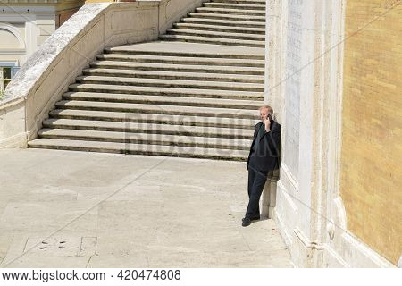 Roma, Italy - April, 15, 2021.catholic Priest Talking On A Cell Phone, Leaning Against The Wall On A