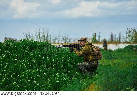 A Soldier In Military Uniform Sits In The Grass And Takes Aim At The Enemy