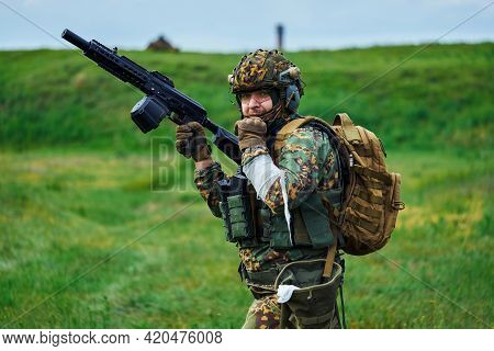 A Soldier In A Military Uniform With A Bandaged Hand Holds A Weapon In His Hand