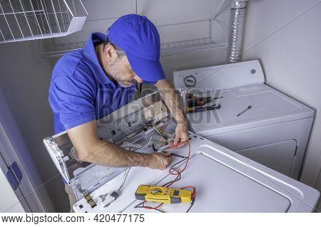 Appliance Service Technician In A Blue Uniform Testing Circuits On A Washing Machine With A Volt Met
