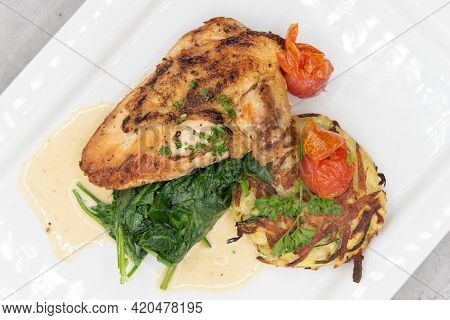Overhead View Of Roasted Chicken Breast Served With Spinach And Hash To Fulfill That Big Appetite.