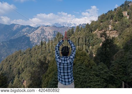 Man On Top Of Green Hill With Both Hands On Top Of Head Respecting Beautiful Nature And Snow Caped M