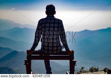 Picture Of Boy Sitting On Ledge On Top Of Mountain. Himachal Pradesh, India