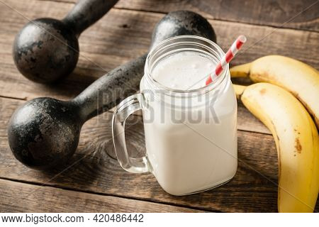 Whey Protein Cocktail, Vintage Dumbbells And Banana Fruit On Wooden Table