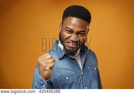 Angry Upset Young Man Clenches Fist Against Yellow Background