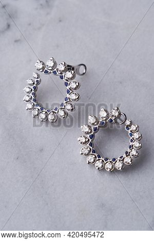 Diamond Earrings On White Marble Background With Copy Space
