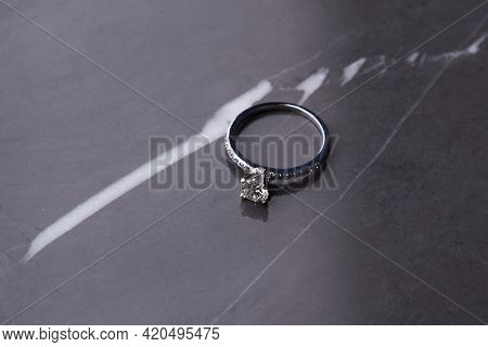 Diamond Ring On Black Marble Background With Copy Space