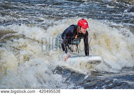 Fort Collins, CO, USA - May 7, 2021: Young male is surfing a wave in the Poudre River Whitewater Park.