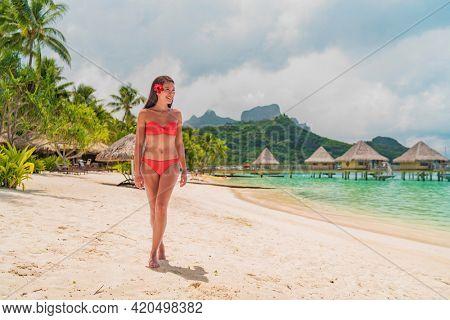 Beach paradise vacation happy Asian bikini woman relaxing walking on dream Bora Bora island travel luxury hotel, Tahiti, French Polynesia. Swimsuit modenatural beauty nature landscape.