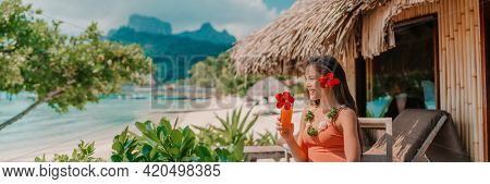 Woman drinking tropical fruits juice morning breakfast at hotel room balcony on beach. Vacation travel in Bora Bora, French Polynesia landscape banner panoramic. Happy tourist enjoying summer holiday.