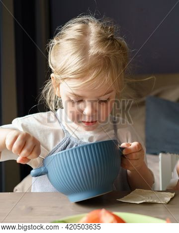 Lunch Time. Cute Child Little Girl With Golden Hair Concentrated On Eating Healthy Food, Kid Sitting