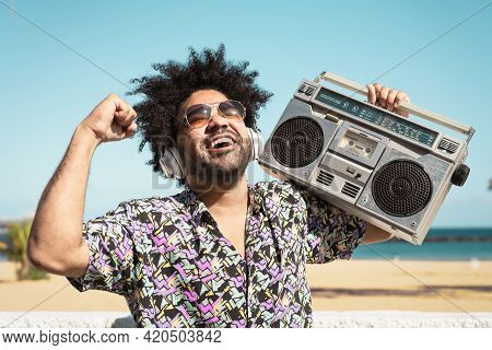 Happy Afro Man Having Fun Listening To Music With Wireless Headphones And Vintage Boombox On The Bea