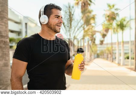 Latin Man Doing Jogging And Workout Routine While Listening Music With Wireless Headphones Outdoor
