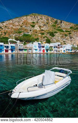 Greek fishing boat in the Aegean sea with picturesque scenic greek Klima village in background, Milos island, Greece