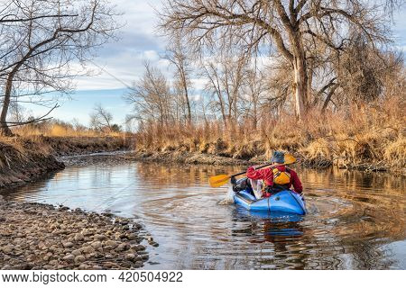 senior male  is paddling an inflatable packraft on a river in early spring spring - Poudre River in northern Colorado