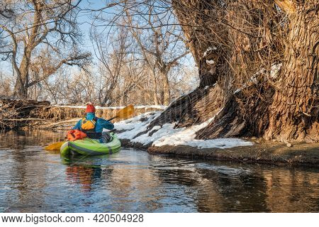male paddler is paddling an inflatable whitewater kayak on a small river - Poudre River in Fort Collins, Colorado, winter or early spring scenery