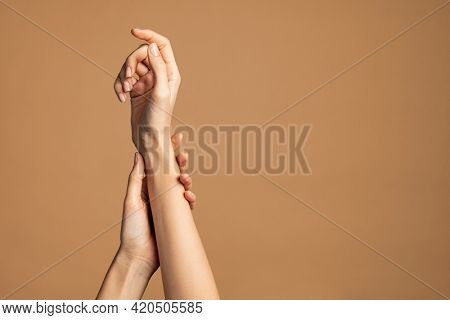 Close up of woman hands isolated on cream brown background with copy space. Smooth female hands applying moisturizer. Beauty gesturing woman's hands with care.