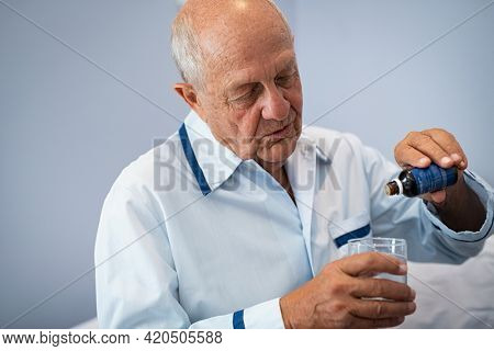 Old man pouring cough syrup in glass at hospital with copy space. Hospitalised elderly man dripping medicine into cup of water for sleep. Senior patient pouring melatonin in glass of water.