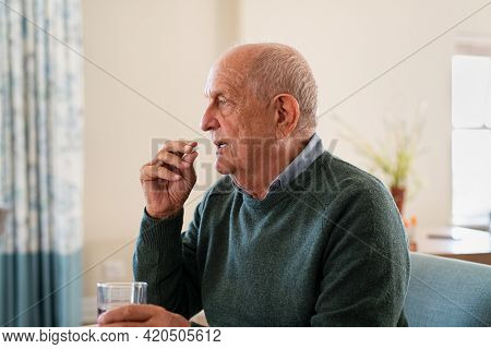 Ill senior man taking medicine at care centre. Elderly man taking pills for depression sitting on couch. Old upset patient swallowing pill with glass of water.