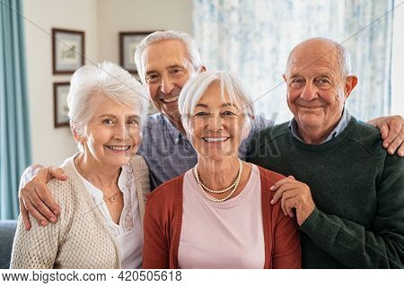 Portrait of happy elderly people looking at camera at care centre. Cheerful senior man and beautiful old woman embracing. Smiling seniors standing together with a big grin on their faces.
