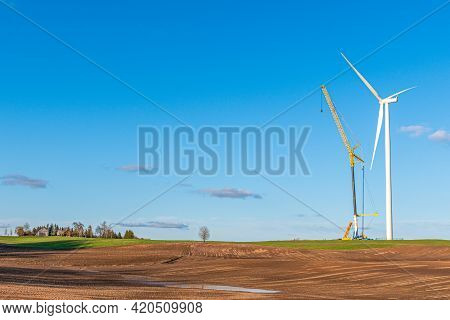 Wind Turbine Under Construction Near A Village In A Agricultural Field With Clear Blue Sky On Backgr