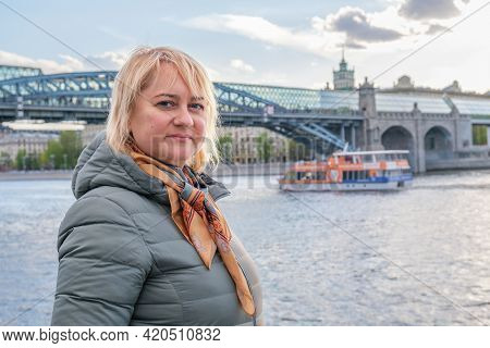 Blonde Middle-aged Woman Stands On Embankment And Looks At Camera Against The Background Of City Bri