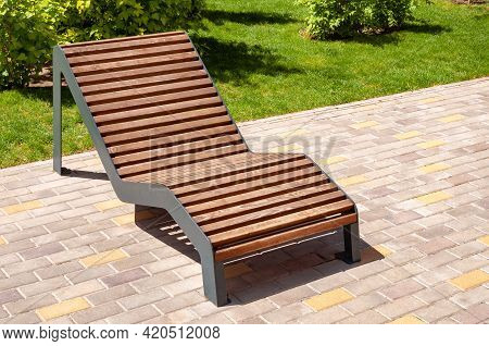 Comfortable Modern Wooden Bench. City Improvement, Urban Planning, Public Spaces. Brown Wooden Bench