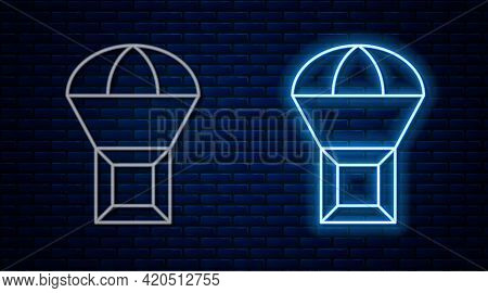 Glowing Neon Line Box Flying On Parachute Icon Isolated On Brick Wall Background. Parcel With Parach