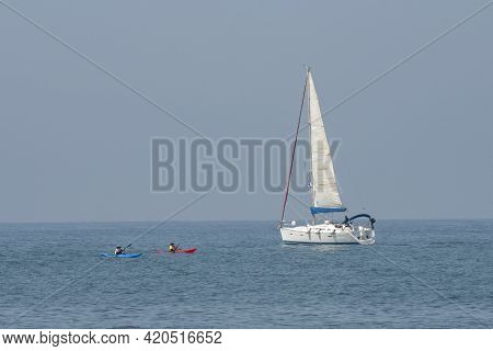 Tel Aviv, Israel - April 15th, 2021: A Sailboat And Two Kayak Of The Shore Of Tel Aviv, Israel, On A