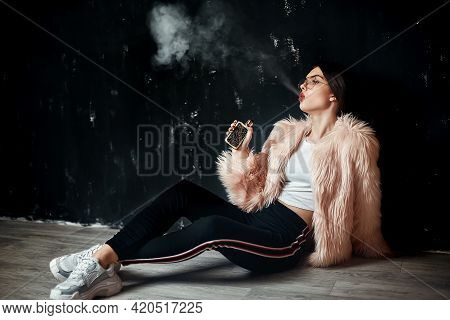 Sexy Trendy Rap Woman In Pink Fur Coat Smoke Electronic Cigarette. Pink Studio Background Shooting